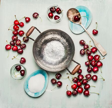 cereza: Ingredientes para preservar la cereza dulce, mermelada o jalea de decisiones, en torno a la olla vacía, vista desde arriba, espacio de copia.