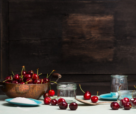 mermelada: Sweet cherry jam and  jelly preserve preparing on rustic wooden background, place for text, kitchen scene