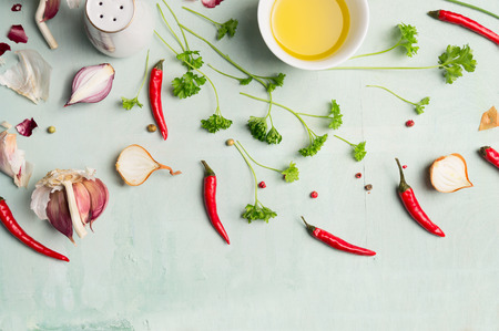 view top: Chili peppers , oil, and fresh herbs and spices for cooking, top view Stock Photo