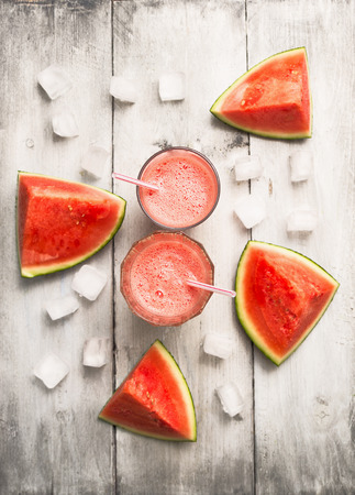 watermeloen sap of smoothie met ijsblokje op rustieke houten achtergrond, bovenaanzicht