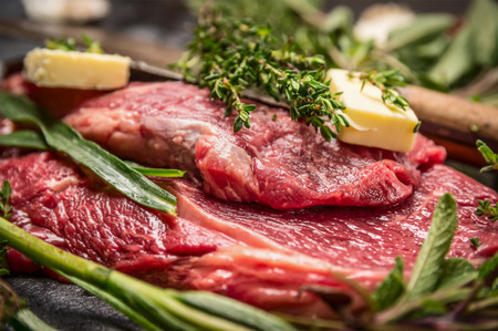 meat food: Raw beef steak with herbs and butter for grill or cooking, close up