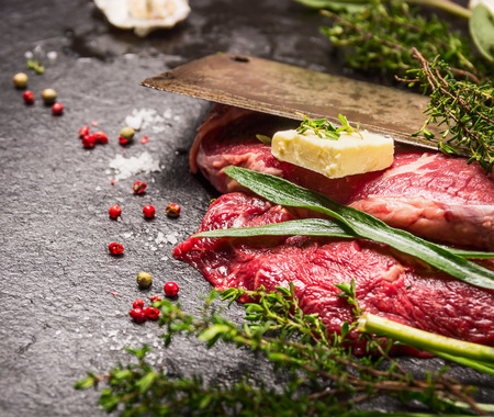 meat food: Raw beef steak. Preparation with old meat cleaver, butter and fresh herbs