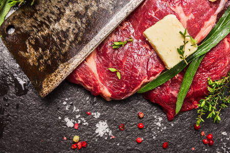 the cleaver: Raw beef steak with old meat cleaver, butter and fresh herbs, top view