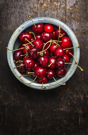 Fresh cherries berries in blue bowl on dark rustic wooden background