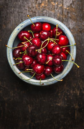 table: Fresh cherries berries in blue bowl on dark rustic wooden background