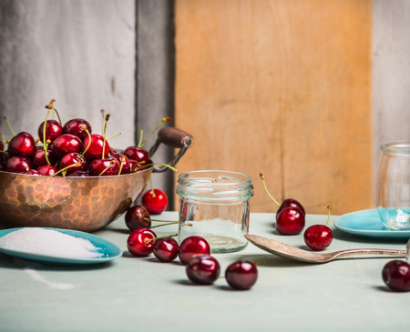 rustic kitchen: Cherries berries preserving with glass jar on rustic kitchen table, over wooden background Stock Photo