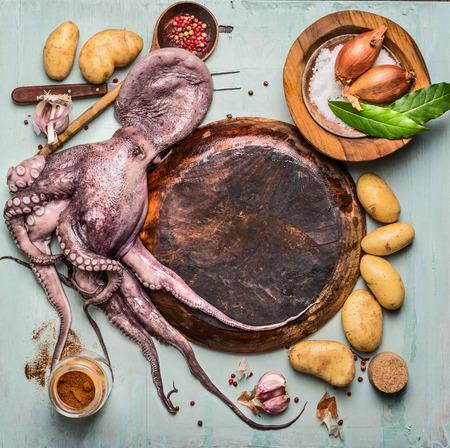 pulpo: Pulpo crudos alrededor de la placa de madera vacía con los ingredientes para cocinar español: patatas y especias en el fondo rústico, vista superior