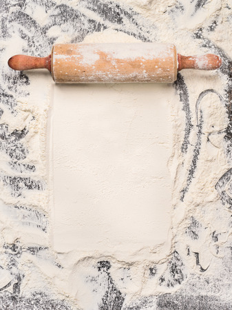 baking background with flour and rustic rolling pin. Top view, place for text. Foto de archivo