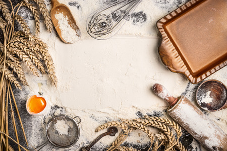 flour baking background with raw egg, rolling pin, wheat ear and rustic bake pan. Top view