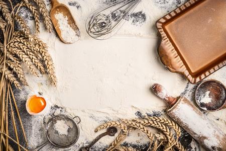 harina de fondo de horno con huevo crudo, palo de amasar, la oreja de trigo y pan horneado rústico. Vista superior Foto de archivo
