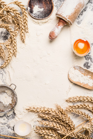 wheat: flour baking background with raw egg, rolling pin and wheat ear , top view