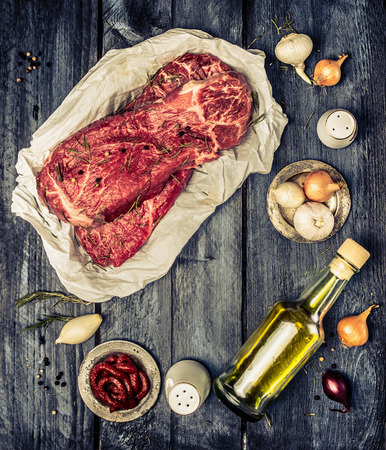 Raw marbled beef meat with ingrredients for cooking on rustic wooden background, top view. Retro toned. Frame. Stock Photo