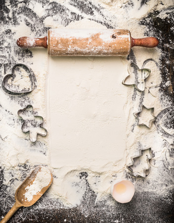 Christmas bake tools on flour and rustic wooden background, top view, place for text Stok Fotoğraf