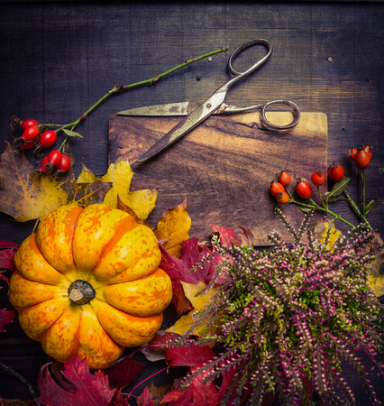 pumpkin with autumn leaves and flowers, vintage  scissors on rustic wooden background, top view