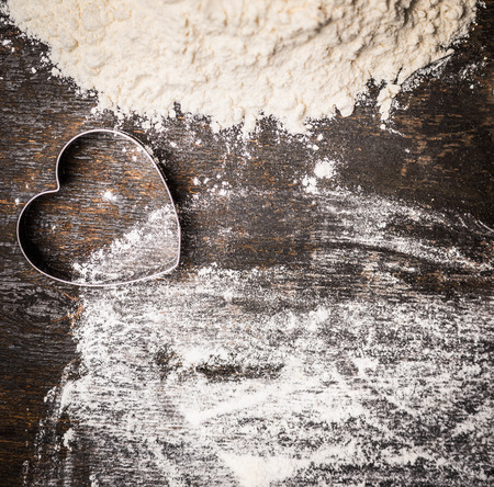 flour: Hornee fondo de madera con forma de corazón el amor cortador de galletas para hornear y la harina, la vista superior
