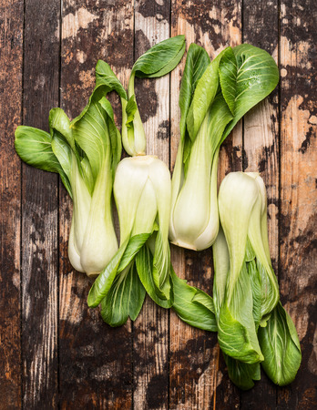 fresh pak choi on rustic wooden background, top view