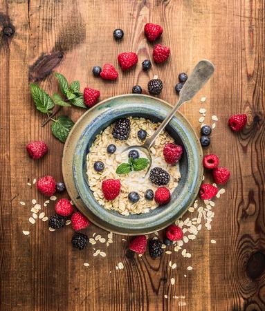 cereales: Gachas de avena con leche, bayas en cuenco rústico en fondo de madera, vista desde arriba Foto de archivo