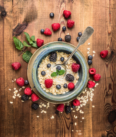 rustic food: Porridge with milk, berries in rustic bowl on wooden background, top view