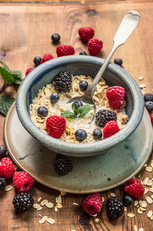 rustic food: Porridge with milk, berries in rustic bowl on wooden background, healthy food concept