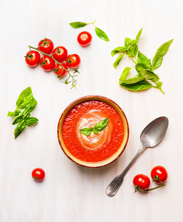 basil: Bowl of tomato soup or gazpacho with spoon and basil on white wooden background, top view Stock Photo