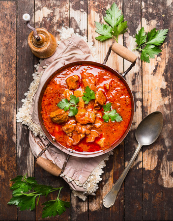 beef stew or goulash in old pan served with spoon and napkin on rustic wooden background, top view Stockfoto