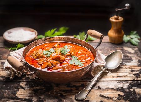 Goulash o guiso en cacerola de cobre con la cuchara en la mesa de la cocina rústica sobre fondo de madera oscura