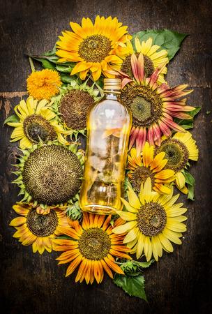 Zonnebloemen en fles olie op donkere houten achtergrond, bovenaanzicht