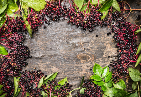 Elderberries with leaves on rustic wooden background, top view,frame