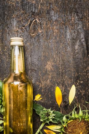 Zonnebloemolie in glazen fles en zonnebloemen op rustieke houten achtergrond, plaats voor tekst Stockfoto