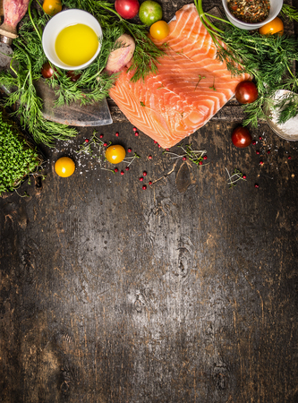 Zalmfilet en ingrediënten voor het koken op een donkere rustieke houten achtergrond, bovenaanzicht. Gezond eten koken concept.