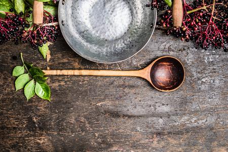 Vlierbessen bos met lege pot en lepel voor het koken op rustieke houten achtergrond, bovenaanzicht Stockfoto