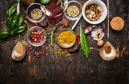 Droge kleurrijke kruiden in de lepels en kommen met verse kruiden op donkere rustieke houten achtergrond, bovenaanzicht, grens Stockfoto
