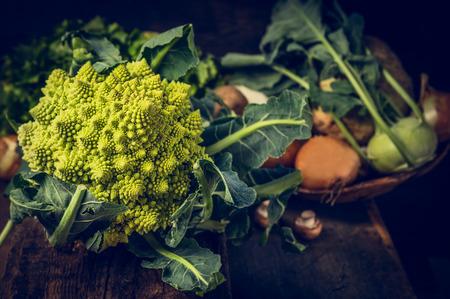 coliflor: Coliflor romanesco en la mesa de la cocina rústica con verduras sobre fondo de madera Foto de archivo