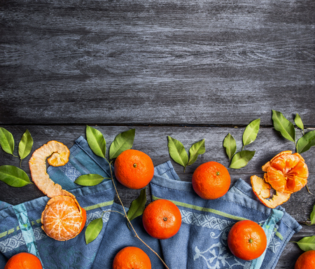 marco madera: Border of mandarins with leaves on blue rustic wooden background, top view