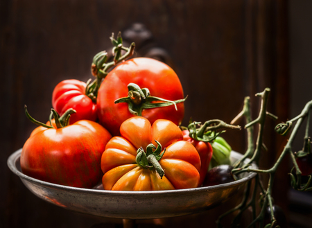 over black: Fresh organic farm tomatoes in steel bowl over dark wooden background, close up Stock Photo
