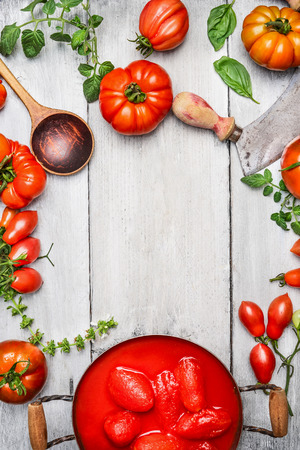 Fresh and some whole peeled tomatoes in cooking pan, basil, wooden spoon and chopper on white rustic wooden background, top view, frame.