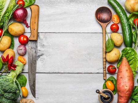 �cooking: Delicioso surtido de vegetales frescos de granja con el cuchillo y la cuchara en el fondo de madera blanco, vista desde arriba. Ingredientes vegetarianos para cocinar. Concepto de cocina saludable.