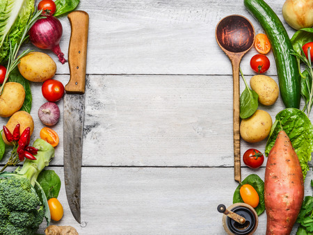 ingredient: Delicious assortment of farm fresh vegetables with knife and spoon on white wooden background, top view. Vegetarian ingredients for cooking. Healthy cooking concept. Stock Photo