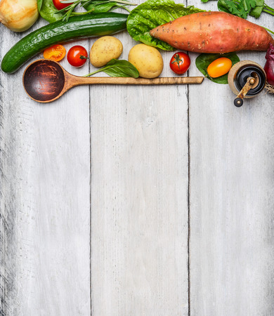 Fresh organic vegetables ingredients and wooden spoon on rustic wooden background, top view. Healthy eating concept. Imagens