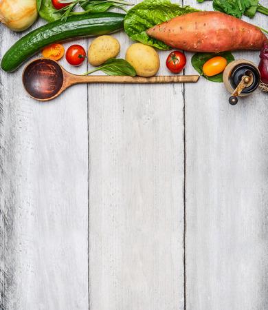 Verse biologische groenten ingrediënten en houten lepel op rustieke houten achtergrond, bovenaanzicht. Gezond eten concept.