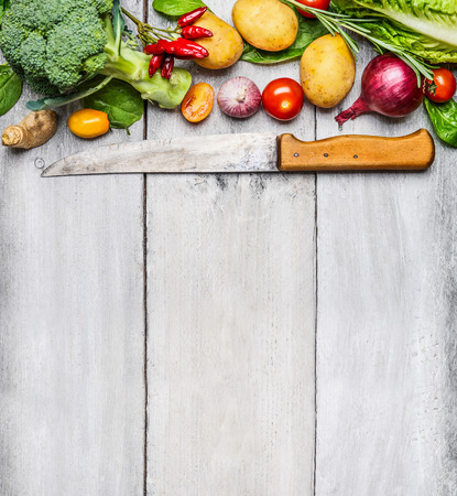 Fresh vegetables ingredients for cooking with used kitchen knife on white wooden background, top view, place for text. Vegan, diet or healthy cooking concept.