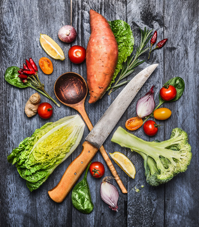 meal preparation: Raw organic vegetables with kitchen knife and selection wooden spoon. Ingredients for healthy cooking on blue rustic wooden background, top view. Stock Photo