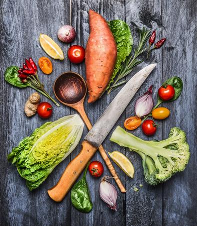 trompo de madera: vegetales orgánicos sin procesar con el cuchillo de cocina y la selección cuchara de madera. Ingredientes para cocinar saludable sobre fondo azul de madera rústica, vista desde arriba. Foto de archivo