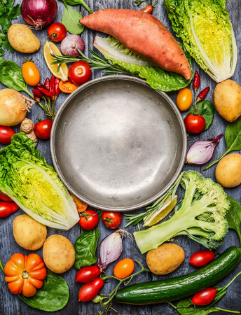 Fresh colorful organic season vegetables ingredients around empty steel  plate on rustic wooden background, top view, copy space. Healthy, diet or vegetarian food concept.