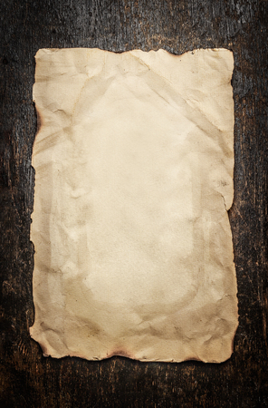 antique paper: Old paper on a aged wooden background, frame