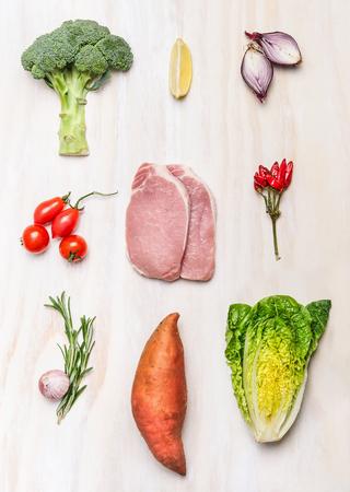 生の肉豚肉ステーキと白い木製の背景、トップ ビューで新鮮な野菜の食材