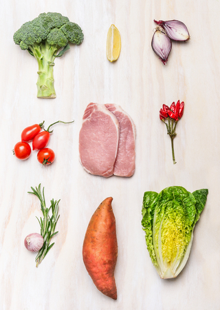 Raw meat pork steak and fresh vegetables ingredients on white wooden background, top view