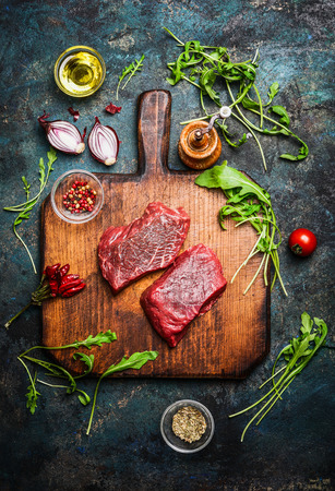 overhead view: Delicious  beef steak on vintage cutting board with fresh various ingredients for tasty cooking on rustic wooden background, top view. Stock Photo