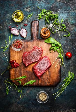 HAMBURGUESA: Filete de carne deliciosa en la tabla de cortar de la vendimia con diversos ingredientes frescos para cocinar sabroso en el fondo de madera rústica, vista desde arriba. Foto de archivo