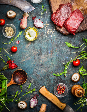 Fresh beef steak, wooden spoon, knife and aromatic herbs, spices and vegetables for cooking , on rustic background, top view, frame. Stock Photo